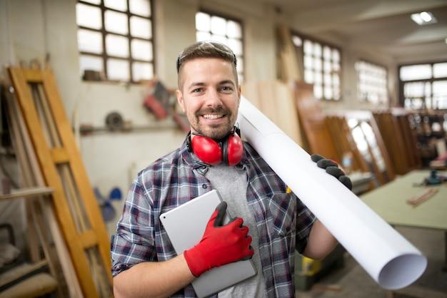 Joven creativo con tableta y papeles en el taller de carpintería