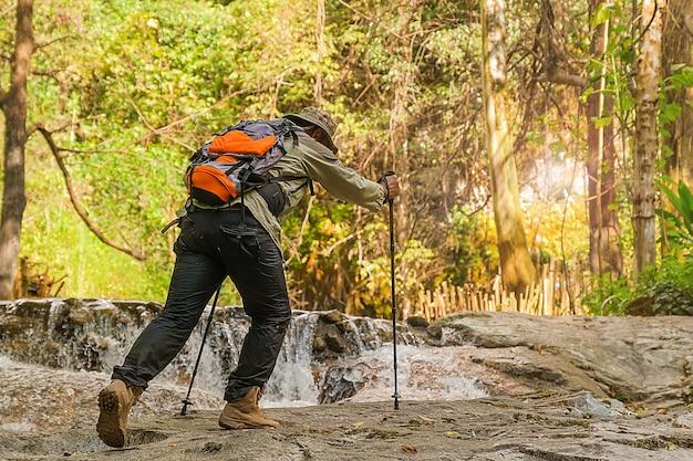 El joven criado con una mochila y bastones de montañismo de pie en las montañas en el verano al aire libre.