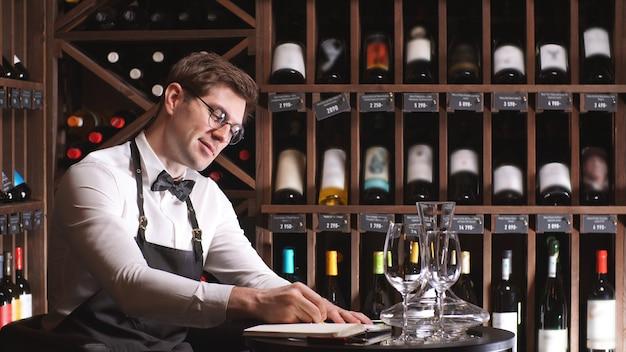 Joven crítico de vinos toma notas en su cuaderno sobre la calidad y el sedimento de una bebida en una tienda de vinos.