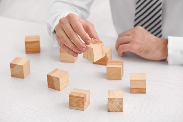 Joven con cubos de madera en la mesa