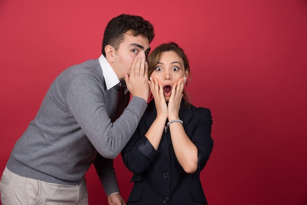 Joven le cuenta algunos rumores de sorpresa a su novia en la pared roja
