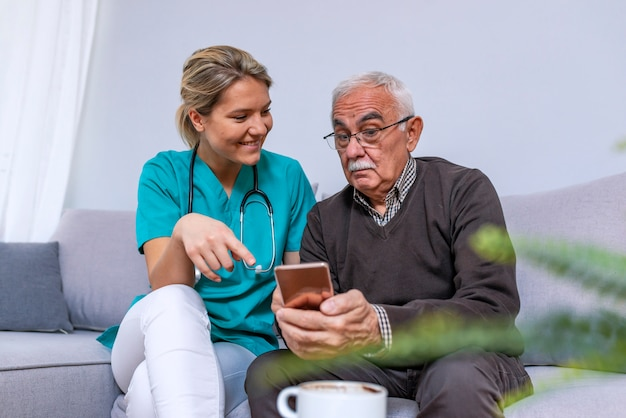 Joven cuidador que muestra al anciano feliz cómo usar el teléfono inteligente