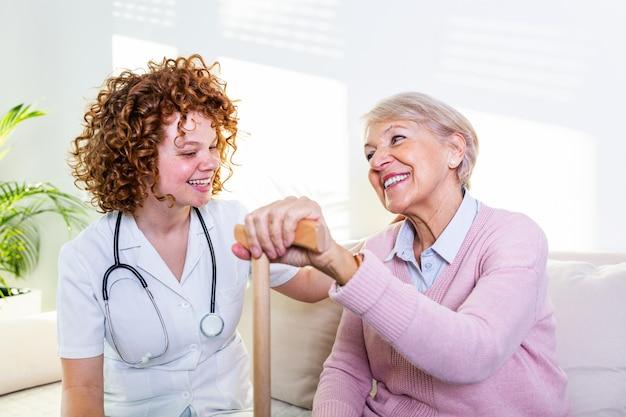 Joven cuidador y senior mujer riendo juntos mientras está sentado en el sofá.