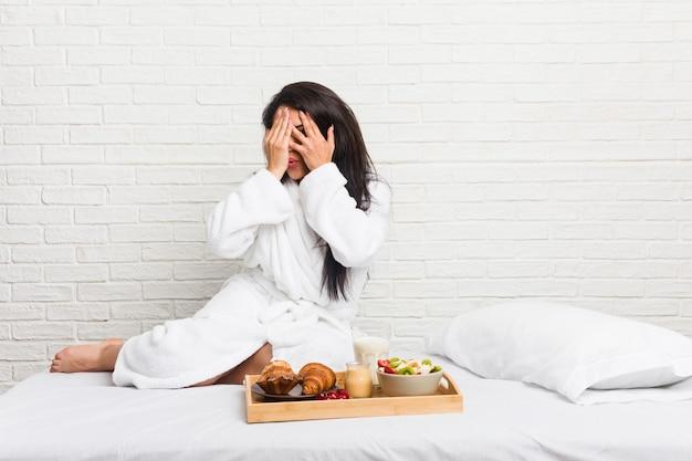 Joven con curvas tomando un desayuno en la cama parpadea entre los dedos asustada y nerviosa.