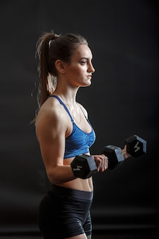Una joven dama deportiva con peinado de cola de caballo en ropa de entrenamiento físico con mancuernas
