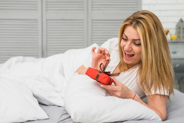 Joven dama feliz con caja actual en la cama