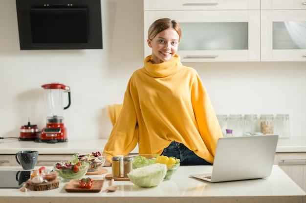 Joven dama feliz sonriendo mientras está de pie en la cocina con un portátil en la mesa frente a ella y cuencos de ensaladas cerca