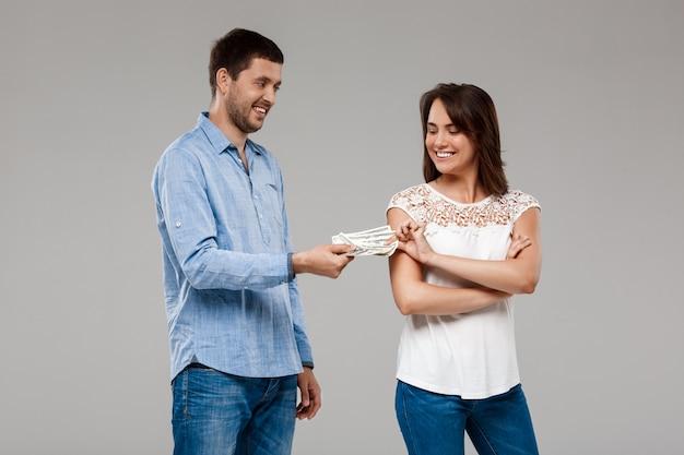 Joven dando dinero a la mujer, sonriendo sobre la pared gris