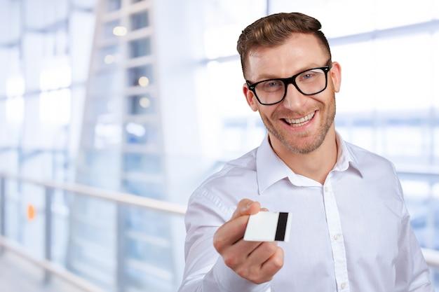 Joven dando su tarjeta de crédito mirando a la cámara
