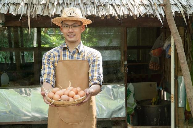 Joven delantal de granjero elegante camisa a cuadros de manga larga delantal marrón tienen huevos frescos de pollo