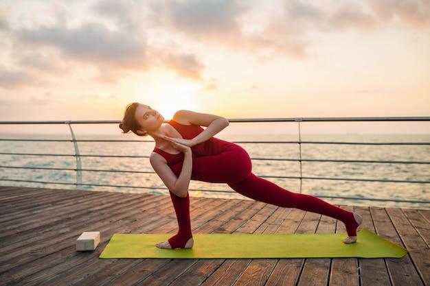 Joven delgada hermosa mujer atractiva haciendo yoga en la mañana al amanecer por el mar, estilo de vida saludable