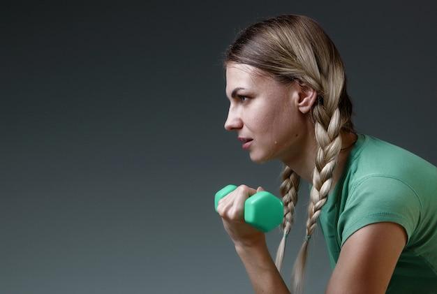 Joven delgada trabaja con pesas pequeñas realizando ejercicios. concepto de un estilo de vida saludable fondo gris luz de estudio