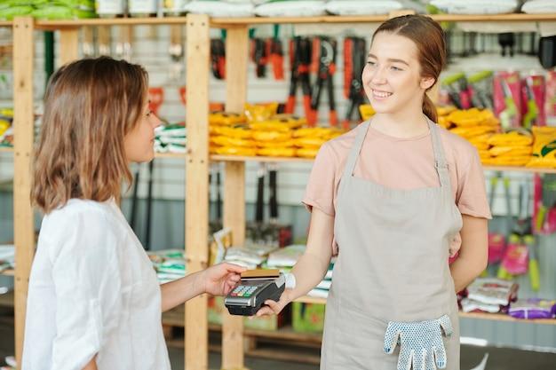 Joven dependienta sonriente en el delantal mirando a la clienta sosteniendo una tarjeta de plástico sobre la pantalla de la terminal de pago mientras compra algo