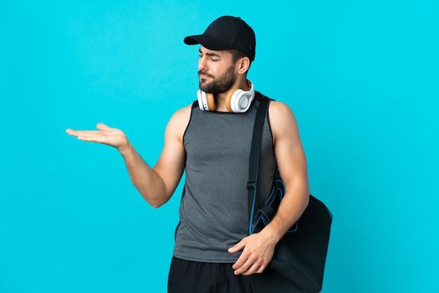 Joven deporte con bolsa de deporte en la pared azul con espacio en blanco con dudas