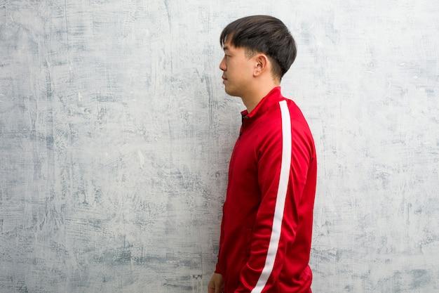 Joven deporte fitness chino en el lado mirando al frente