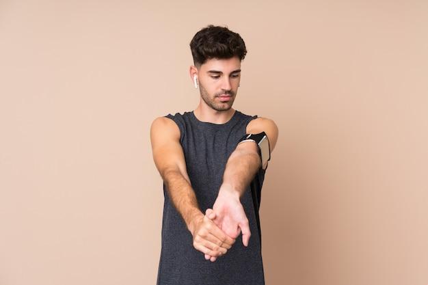 Joven deporte hombre estirando el brazo