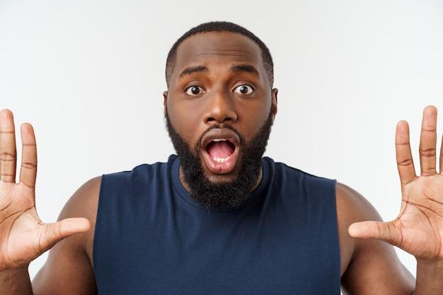 Joven deporte hombre negro sobre un gris muy sorpresa.