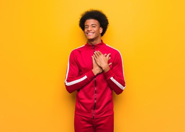 Joven deporte hombre negro sobre una pared naranja haciendo un gesto romántico