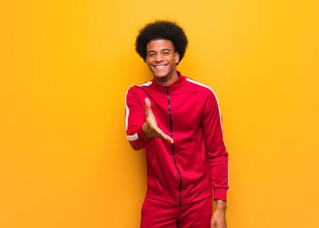 Joven deporte hombre negro sobre una pared naranja llegando a saludar a alguien