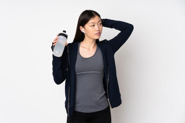 Joven deporte mujer asiática en pared blanca con botella de agua deportiva