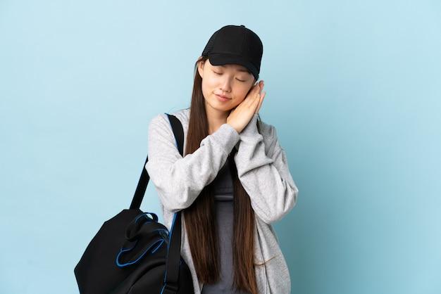 Joven deporte mujer china con bolsa de deporte sobre pared azul haciendo gesto de sueño en expresión dorable