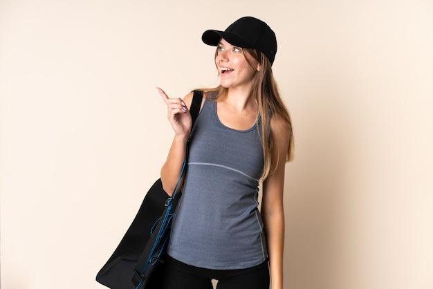 Joven deporte mujer lituana sosteniendo una bolsa de deporte aislada en beige con la intención de darse cuenta de la solución mientras levanta un dedo hacia arriba