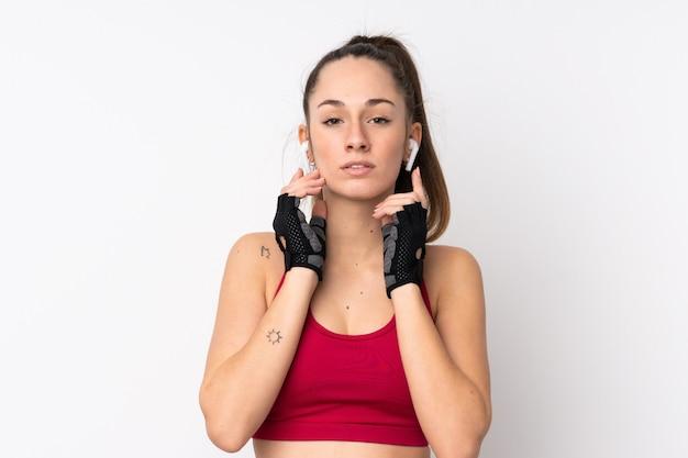 Joven deporte mujer morena sobre pared blanca aislada escuchando música y mirando hacia el frente