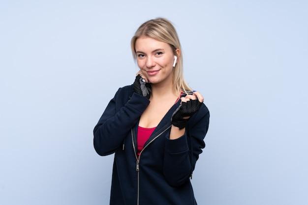 Joven deporte mujer rubia escuchando música y mirando hacia el frente