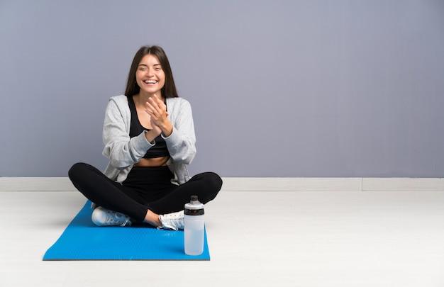 Joven deporte mujer sentada en el suelo con alfombra aplaudiendo