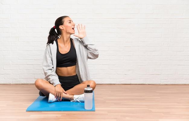 Joven deporte mujer sentada en el suelo con estera gritando con la boca abierta