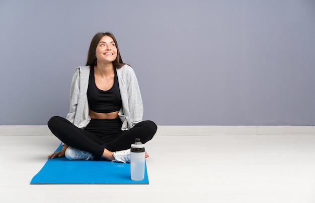 Joven deporte mujer sentada en el suelo con estera riendo y mirando hacia arriba
