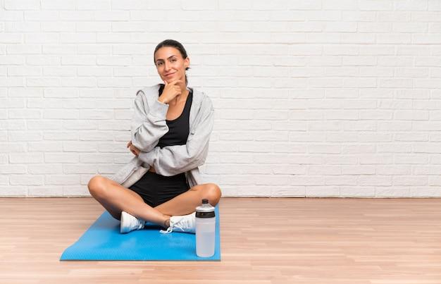 Joven deporte mujer sentada en el suelo con estera riendo
