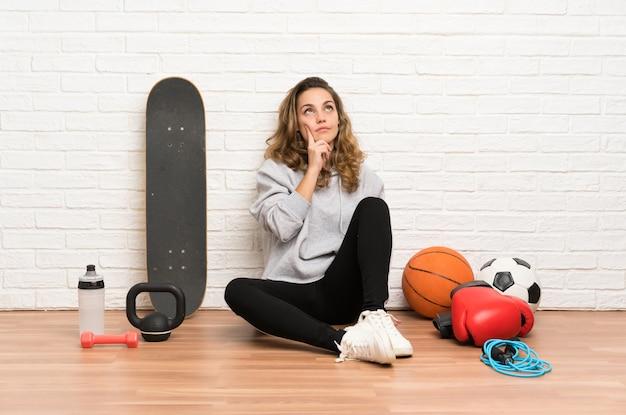 Joven deporte mujer sentada en el suelo pensando en una idea