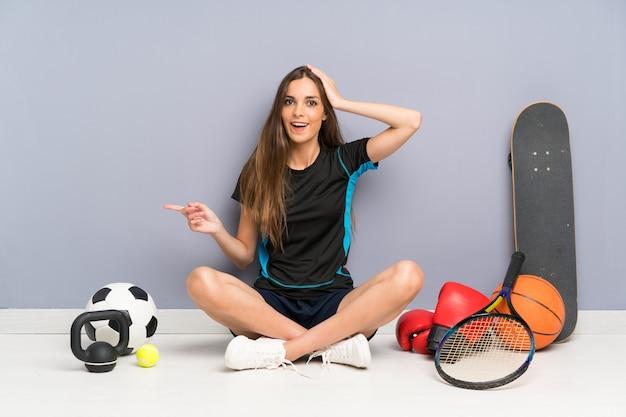 Joven deporte mujer sentada en el suelo sorprendido y apuntando con el dedo al lado