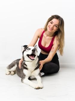 Joven deporte niña con su perro sentado en el suelo