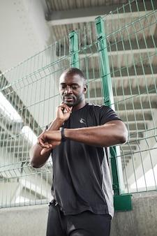 Joven deportista africano con brazalete de fitness tocando su cuello y midiendo el pulso durante la práctica de deportes ...