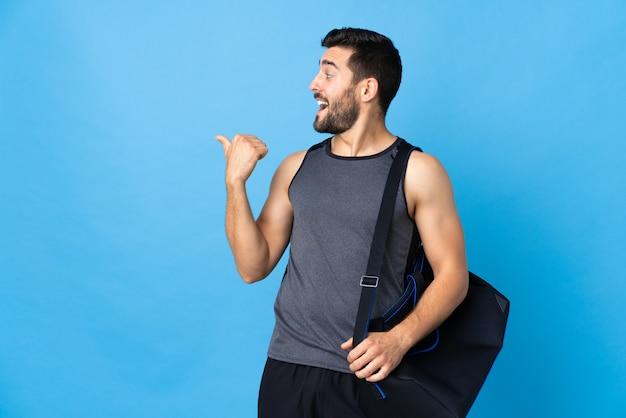 Joven deportista con bolsa de deporte en la pared azul apuntando hacia un lado para presentar un producto