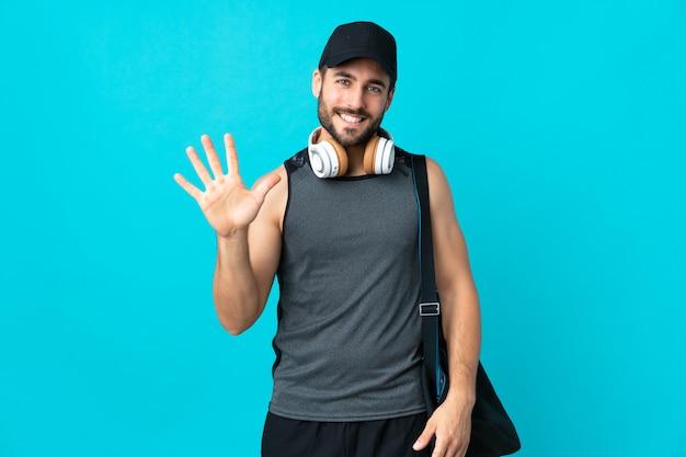 Joven deportista con bolsa de deporte en la pared azul contando cinco con los dedos