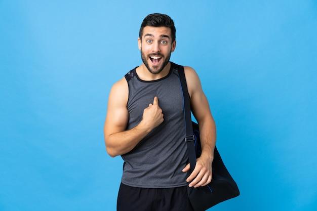Joven deportista con bolsa de deporte en la pared azul con expresión facial sorpresa