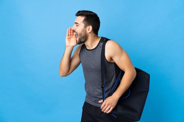 Joven deportista con bolsa de deporte en la pared azul gritando con la boca abierta a un lado