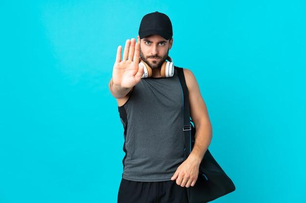 Joven deportista con bolsa de deporte en la pared azul haciendo gesto de parada