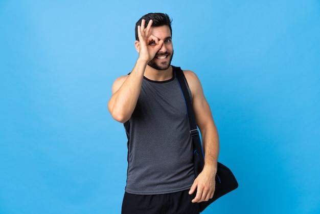 Joven deportista con bolsa de deporte en la pared azul que muestra bien firmar con los dedos