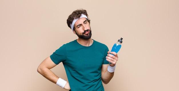 Joven deportista con una botella de bebida energética en pared plana