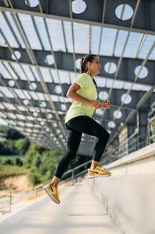Joven deportista en camiseta amarilla y pantalón negro trotar en pasos al aire libre.