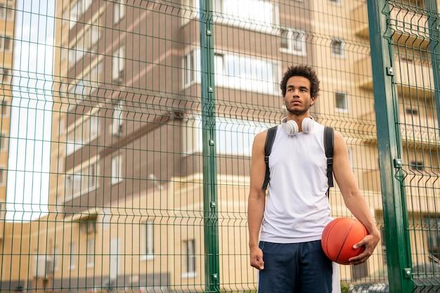 Joven deportista en camiseta blanca con pelota para jugar baloncesto de pie junto a la valla que rodea la cancha