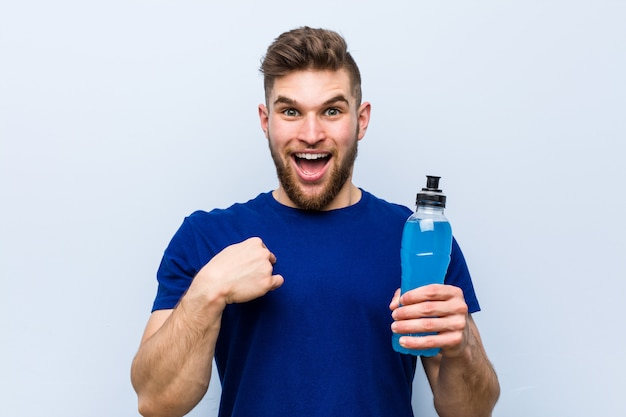 Joven deportista caucásico con una bebida isotónica sorprendido señalando a sí mismo, sonriendo ampliamente.