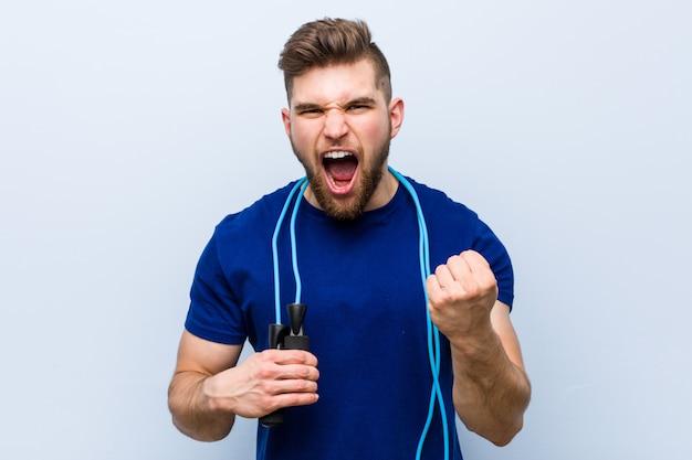 Joven deportista caucásico con una cuerda de saltar animando despreocupado y emocionado. concepto de victoria