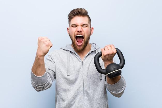 Joven deportista caucásico sosteniendo una pesa animando despreocupado y emocionado. concepto de victoria