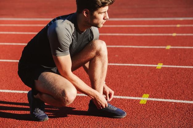 Joven deportista concentrado atando cordones
