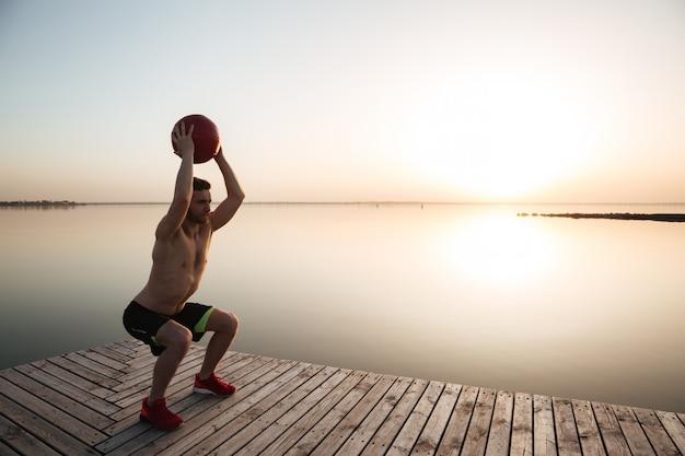 Joven deportista concentrado hacer ejercicios deportivos con balón